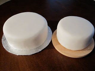 Two cakes side by side covered in white fondant.