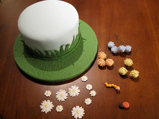 Cake with fondant flowers and bugs ready to be placed on it.