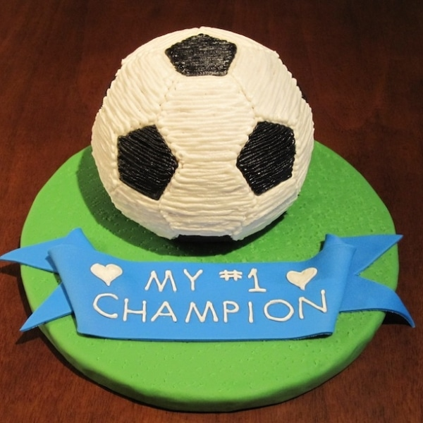 Soccer ball cake on a green cake board with a blue ribbon that says My #1 Champion.