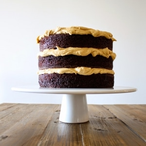 A cake on a white cake stand sitting on top of a wooden table