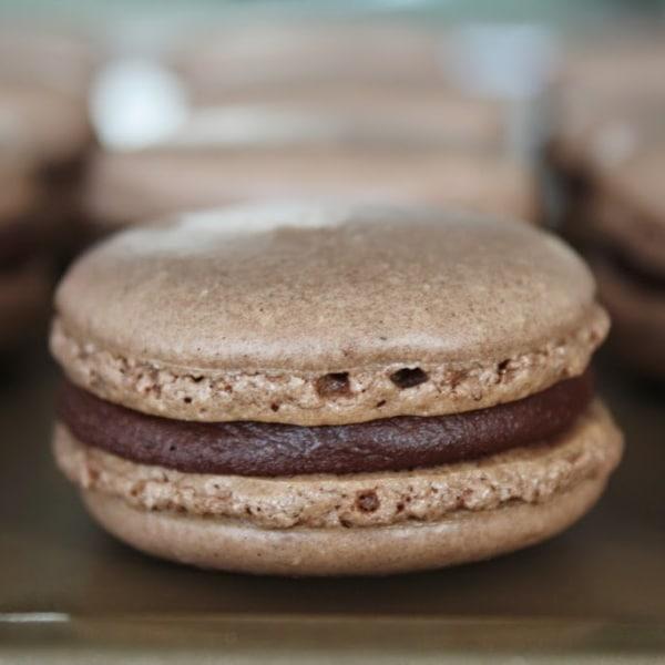 A close up of a chocolate macaron
