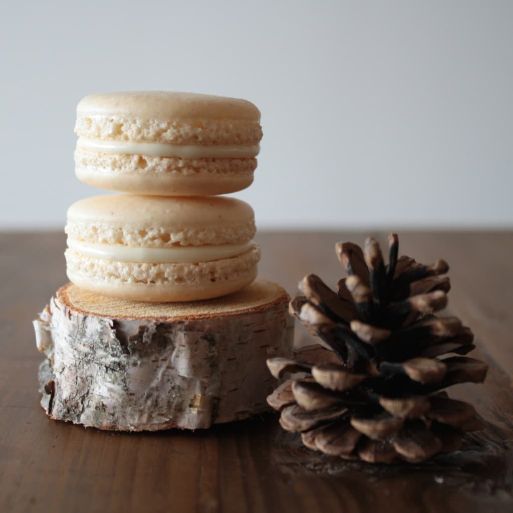 Two eggnog macarons stacked.