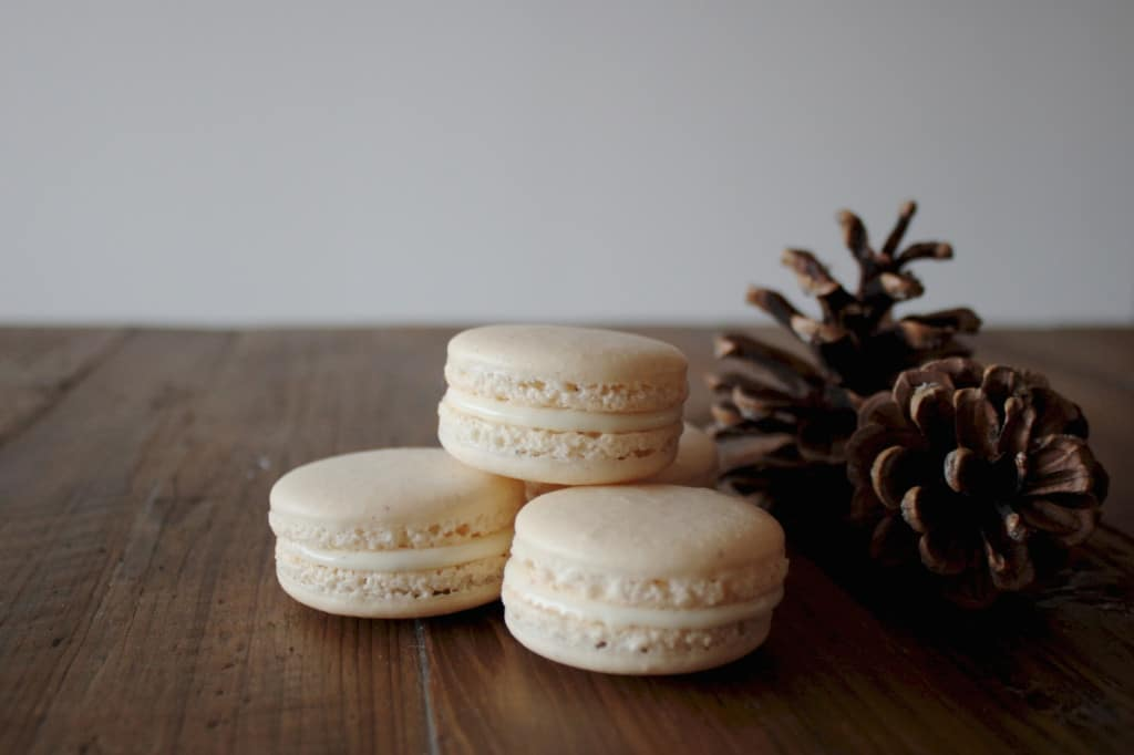 Eggnog macarons on a wood table.