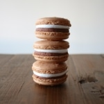 Stack of macarons on a wooden table.