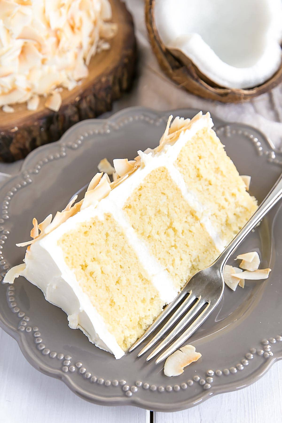 Slice of coconut cake with toasted coconut flakes.