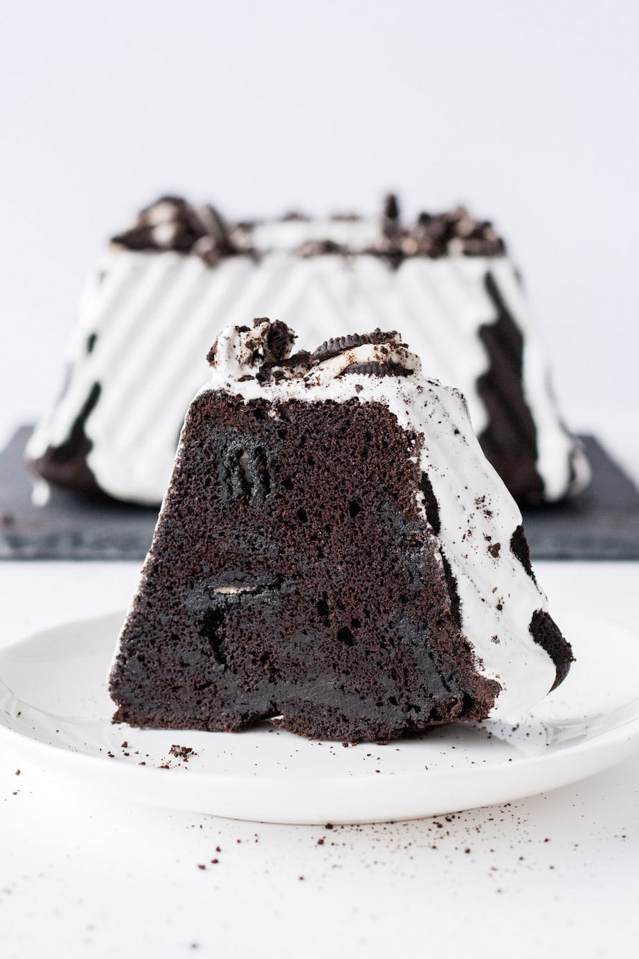 A dark, chocolate Oreo bundt cake with a marshmallow glaze and topped with chopped Oreos. | livforcake.com