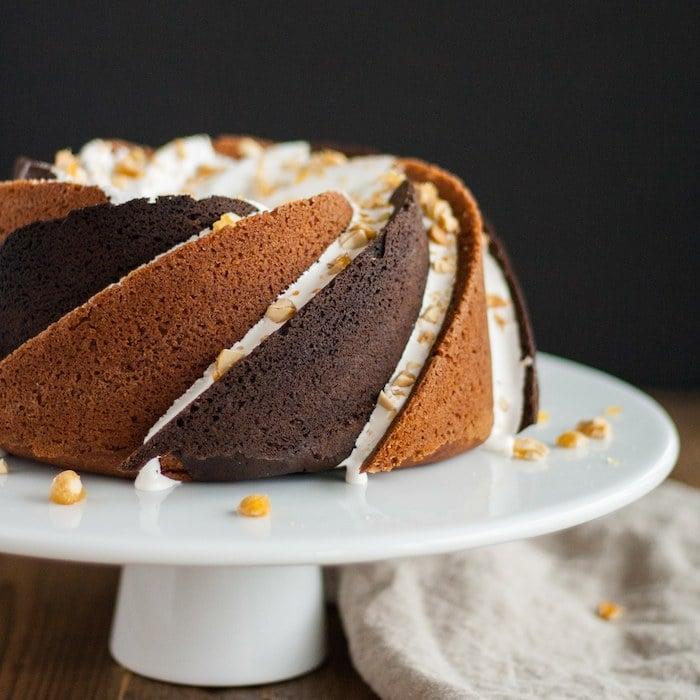 Rocky road bundt cake on a white cake stand.