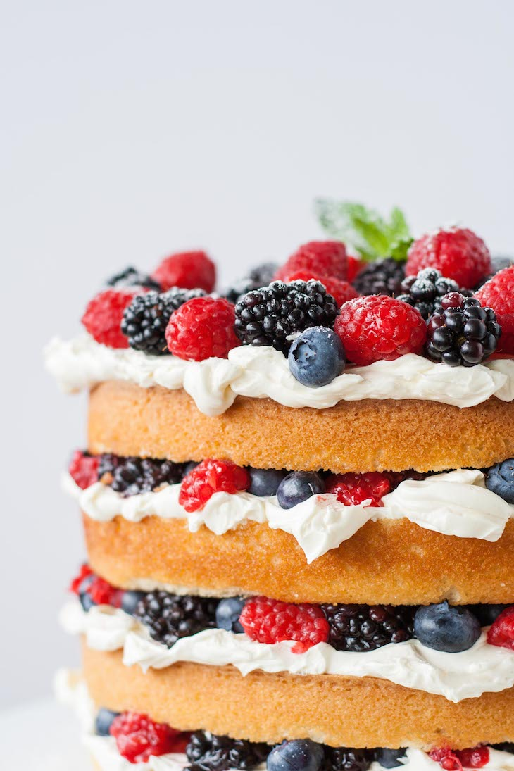 This Very Berry Layer Cake makes the perfect use of those summer berries! Layers of vanilla cake, swiss meringue buttercream, and loads of fresh berries. | livforcake.com