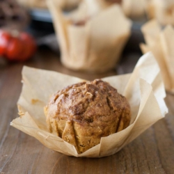 Close up of a pumpkin muffin with the parchment liner peeled back.