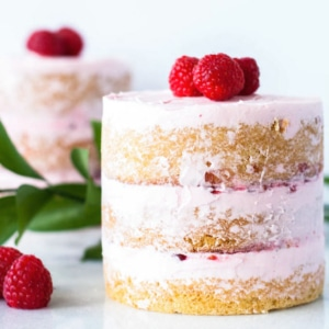 Two mini cakes decorated with fresh raspberries.