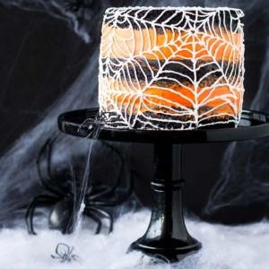 This spiderweb cake is perfect for Halloween! A rich black cocoa cake with an orange flavoured buttercream.   livforcake.com