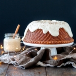 A bundt cake on a white cake stand sitting on top of a wooden table.