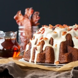 Bundt cake with maple syrup and bacon in the background.