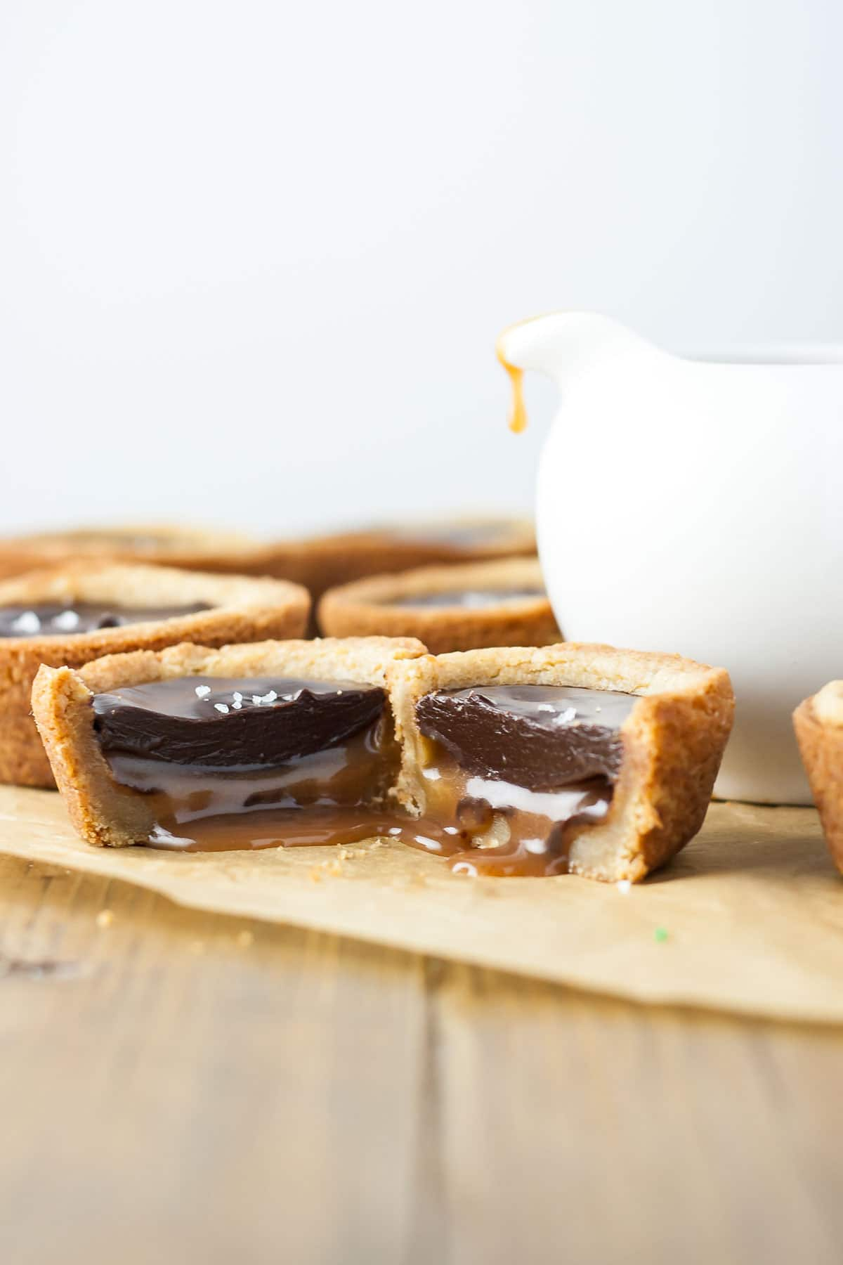 Two cookie cup halves beside each other with caramel oozing out.