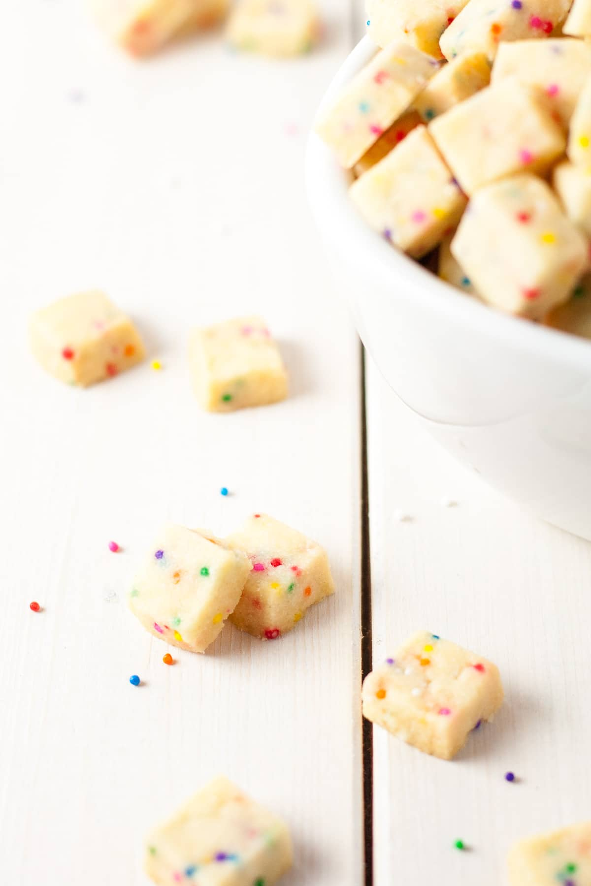 Teeny tiny shortbread cookies studded with rainbow sprinkles. So addictive, the kids will love these! A simple change in the color of the sprinkles and you're set for any holiday or event. | livforcake.com