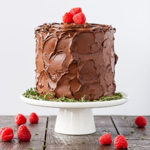 Chocolate covered cake on a white cake stand with fresh raspberries around it.