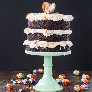 A cake sitting on top of a mint green cake stand. Creme eggs scattered all around.