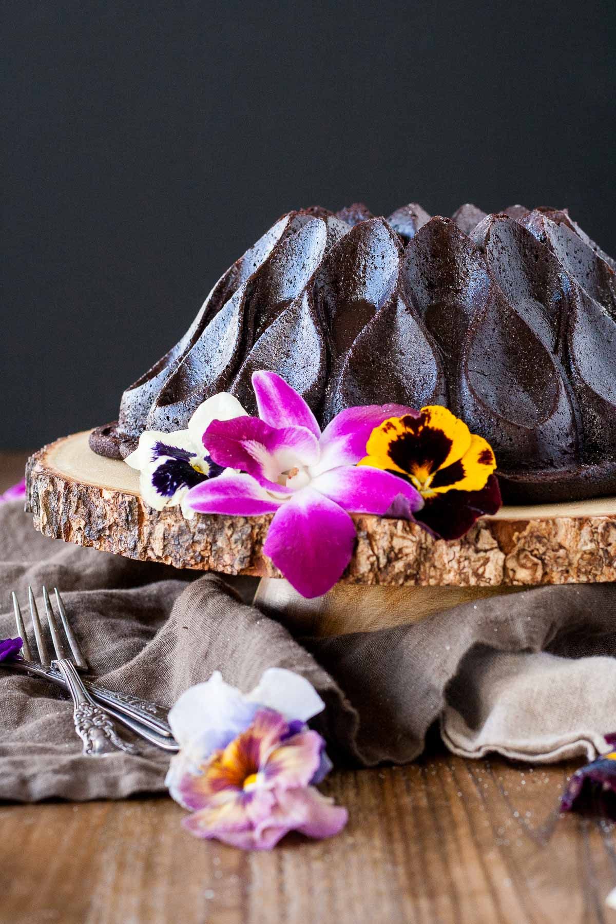 Chocolate Bundt cake on a wooden cake stand garnished with fresh edible flowers.