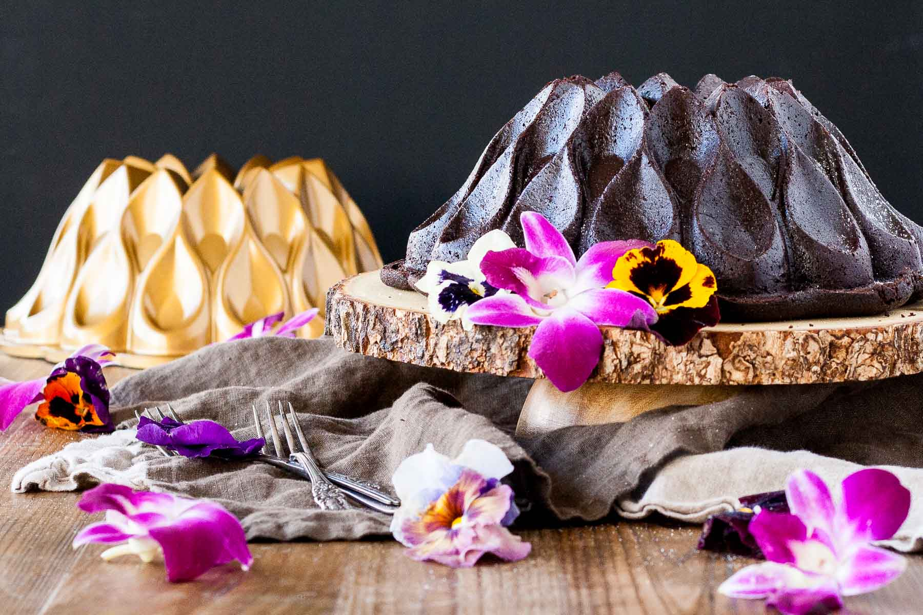 Chocolate Bundt cake on a wooden cake stand garnished with fresh edible flowers. Gold bundt pan in the background.