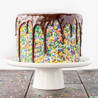This sprinkle studded Funfetti Cake is paired with a fluffy cream cheese frosting and topped with a rich dark chocolate ganache. | livforcake.com