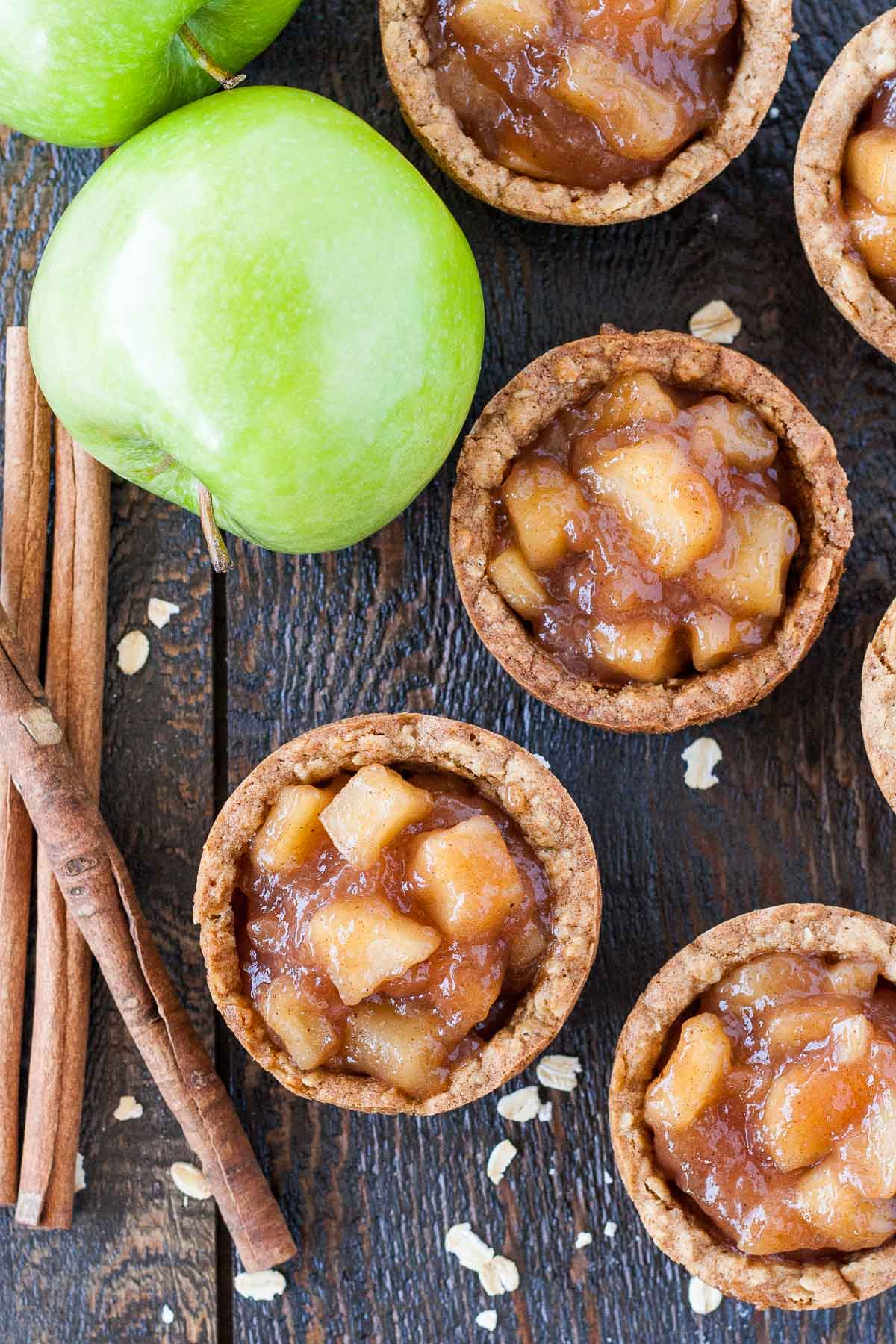 Overhead photo of apple crisp cookie cups with apples and cinnamon sticks on the side.
