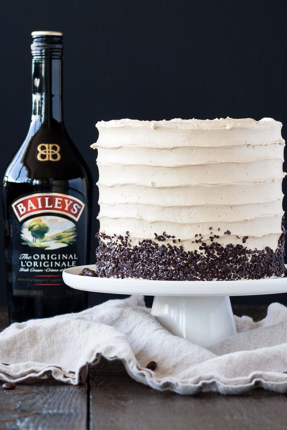 Cake on a white cake stand with a bottle of Baileys behind it.