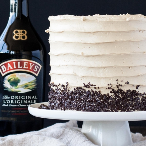 Cake on a white cake stand with a bottle on Baileys behind it.