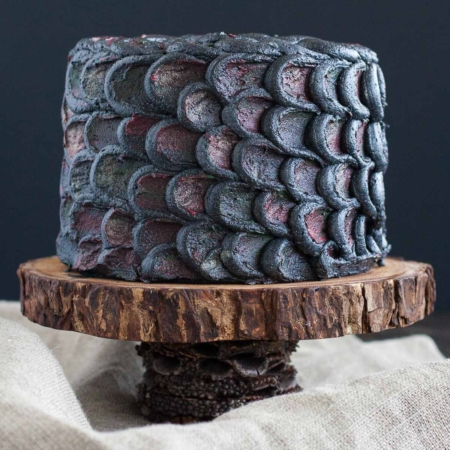 Cake decorated with dragonscales on a rustic cake stand.