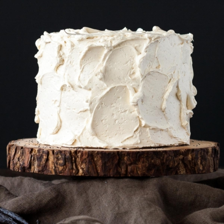 Cake on top of a rustic wood cake stand.