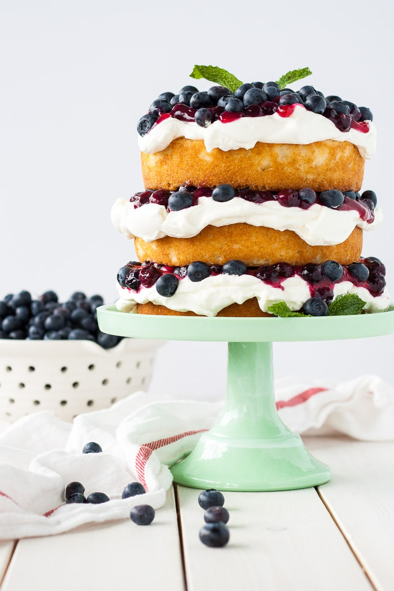 Blueberry shortcake decorated in a rustic, naked cake style on a green cake stand with a bowl of blueberries to the side.
