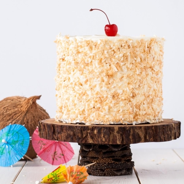 Cake on a rustic wood cake stand with paper drink umbrellas next to it.