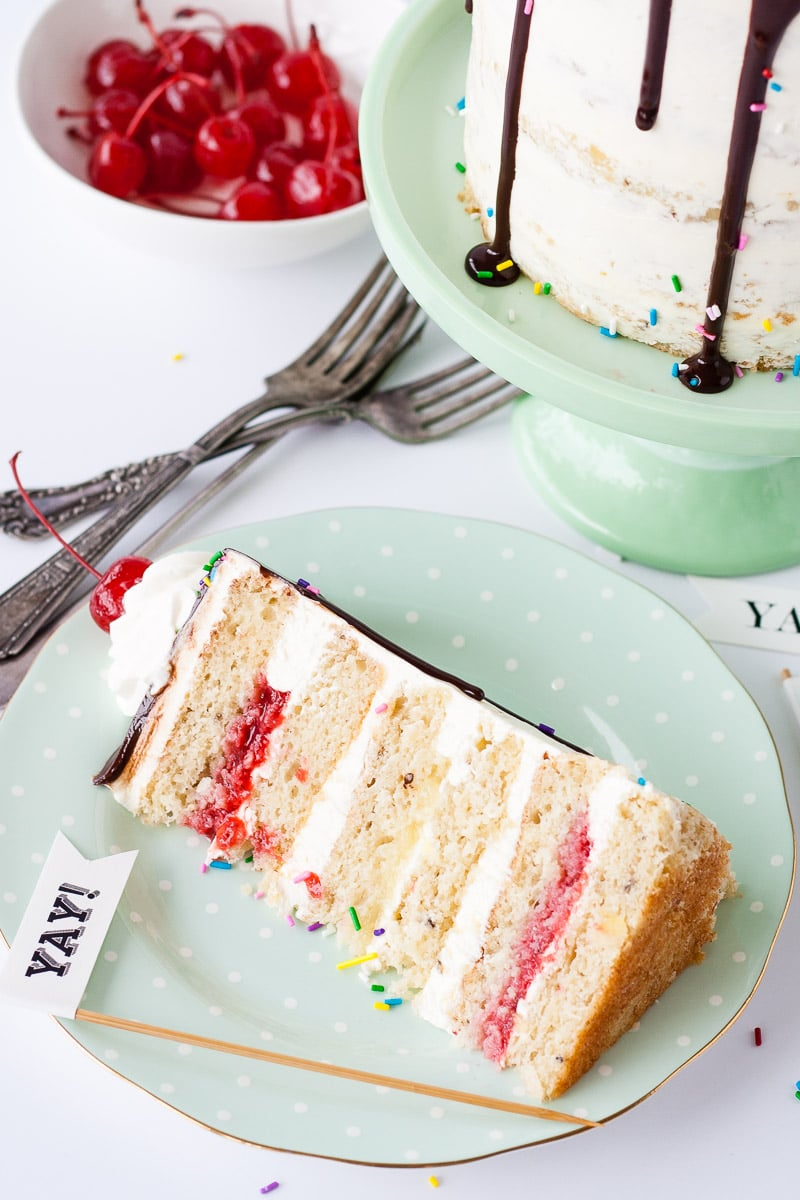 Put a fun new spin on a classic ice cream treat with this decadent Banana Split Cake! Banana cake, vanilla buttercream, strawberry and pineapple fillings, topped off with chocolate ganache, sprinkles, whipped cream, and maraschino cherries!   livforcake.com