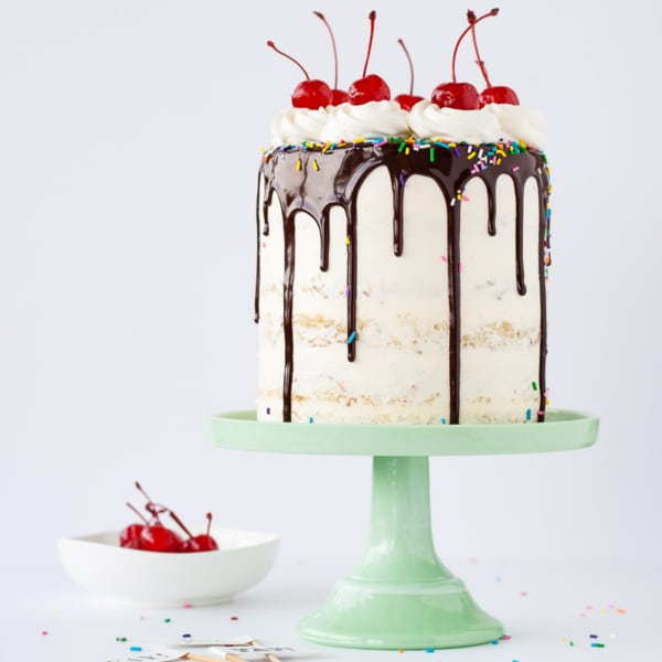 A cake sitting on top of a mint green cake stand with a small bowl of cherries beside it.