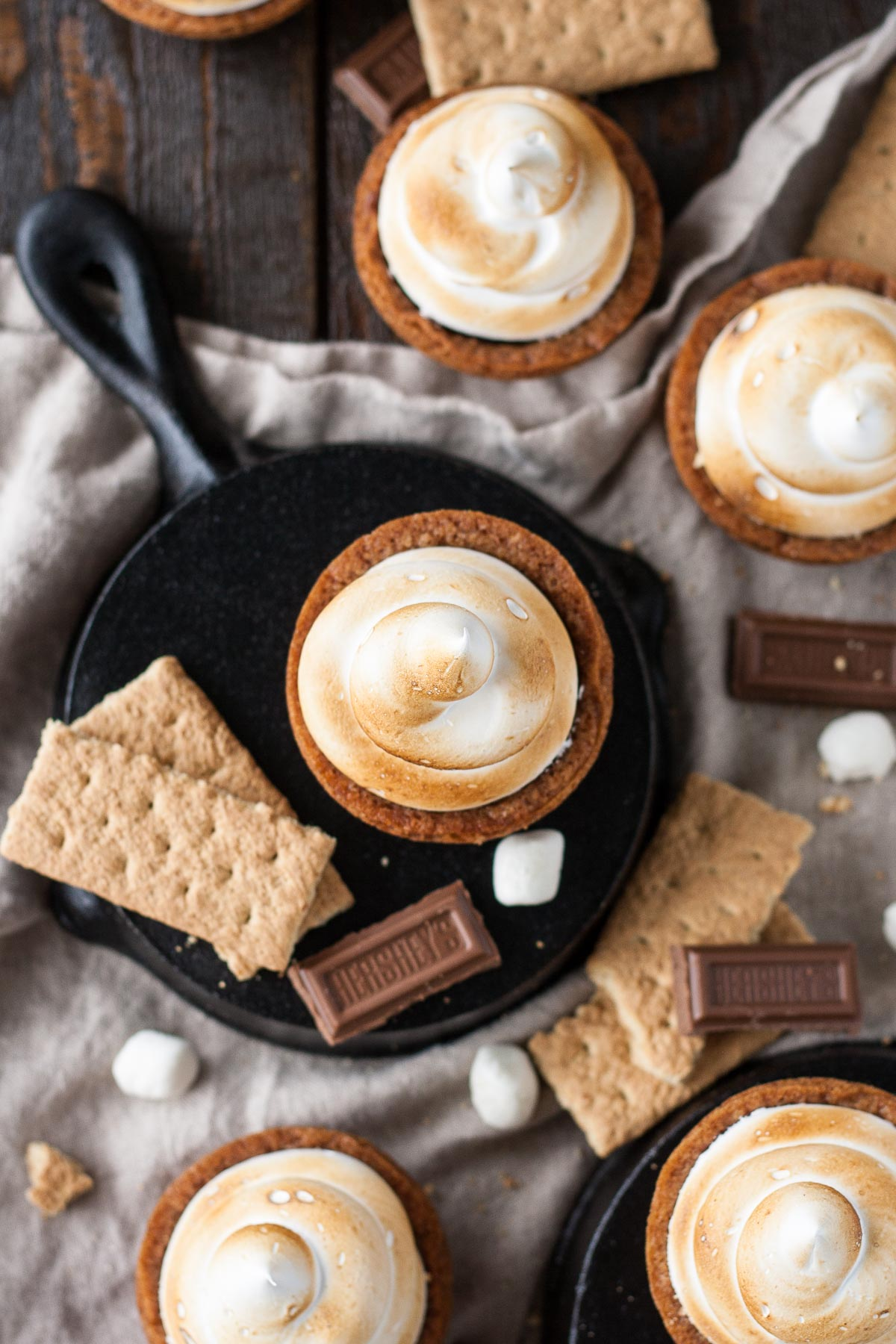 No campfire needed for these S'mores Cookie Cups! Graham cracker cookie cups filled with a Hershey's milk chocolate ganache, topped with toasted homemade marshmallow fluff. | livforcake.com