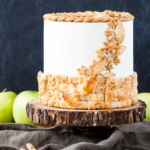 A cake sitting on top of a rustic wooden cake stand with apples in the background.