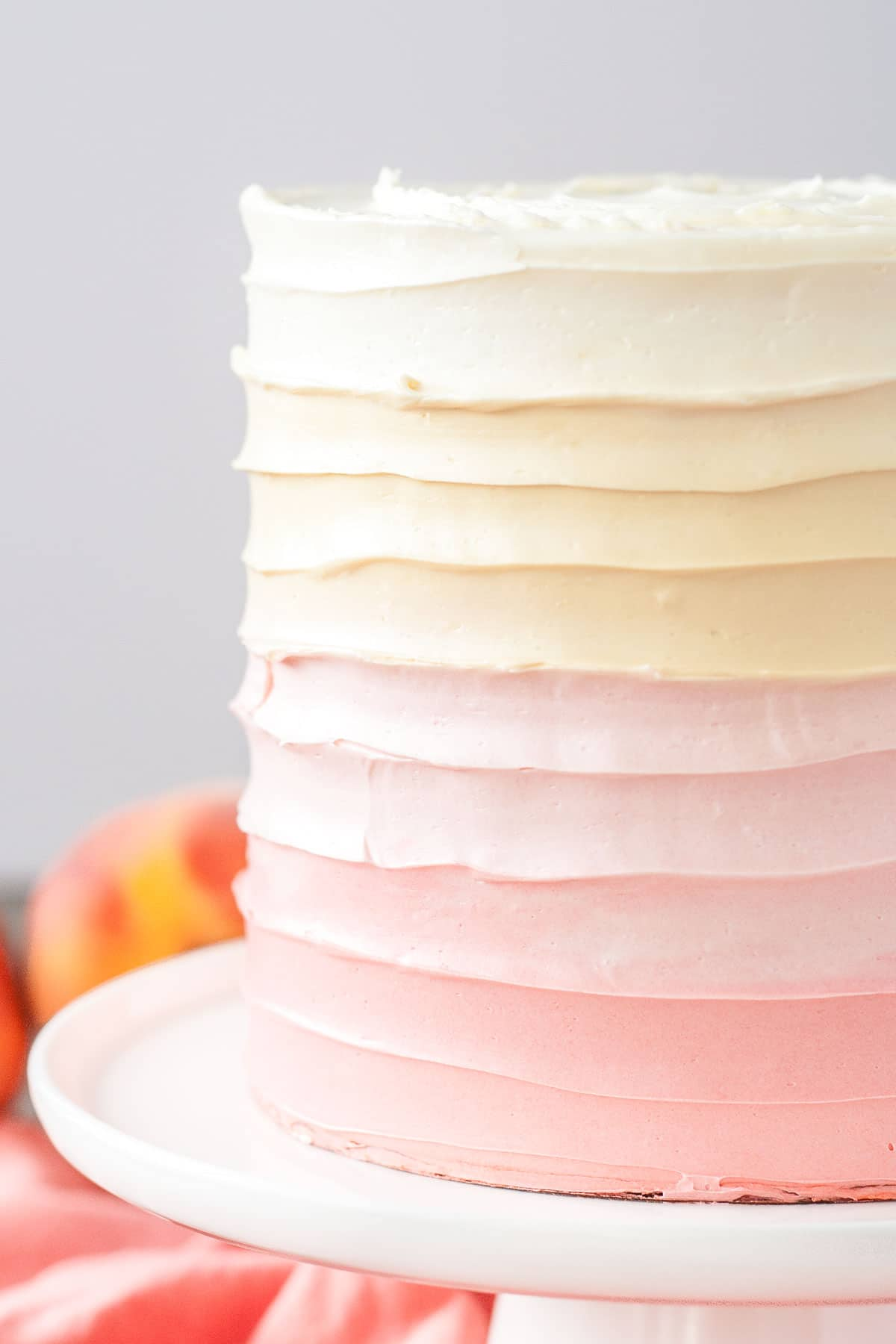 Close up of the swirl frosting technique on an ombre peach cake.