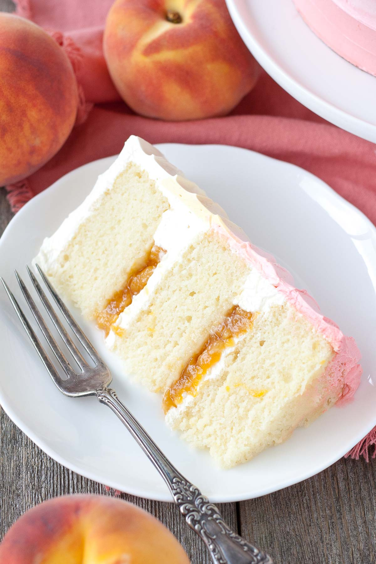 Pretty in Peach! This Peach Layer Cake is the perfect way to wrap up the summer months and make the most of stone fruit season. Vanilla cake with a peach filling and peach flavoured frosting. | livforcake.com