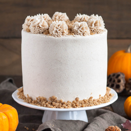 Cake on a cake stand with fall decor in the background.