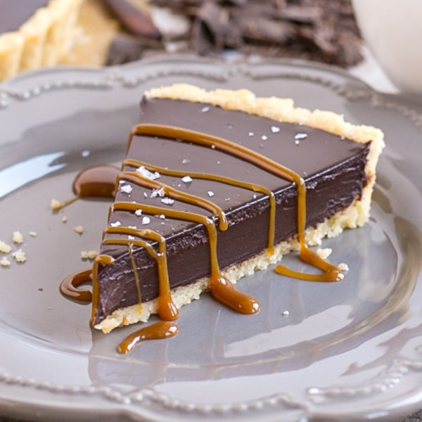 Slice of chocolate ganache tart on a plate with caramel drizzle.