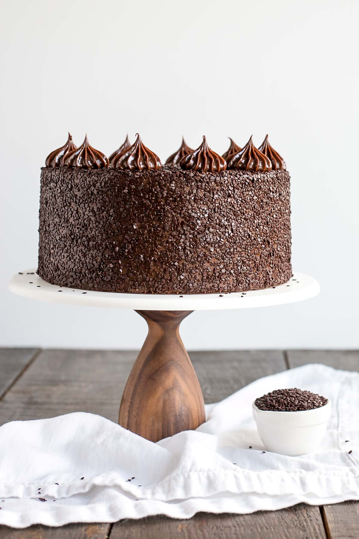 Chocolate cake on a white cake stand.