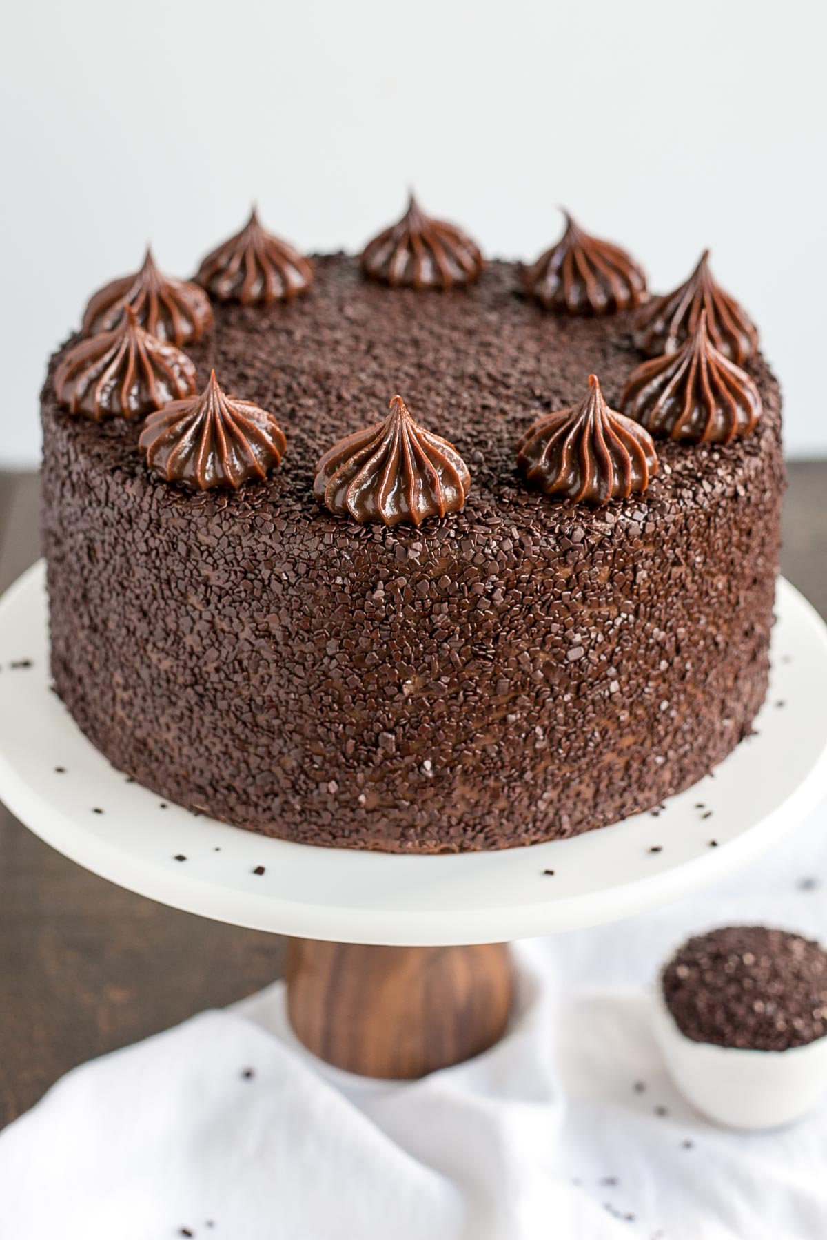 A close up of a chocolate cake on a white cake stand.