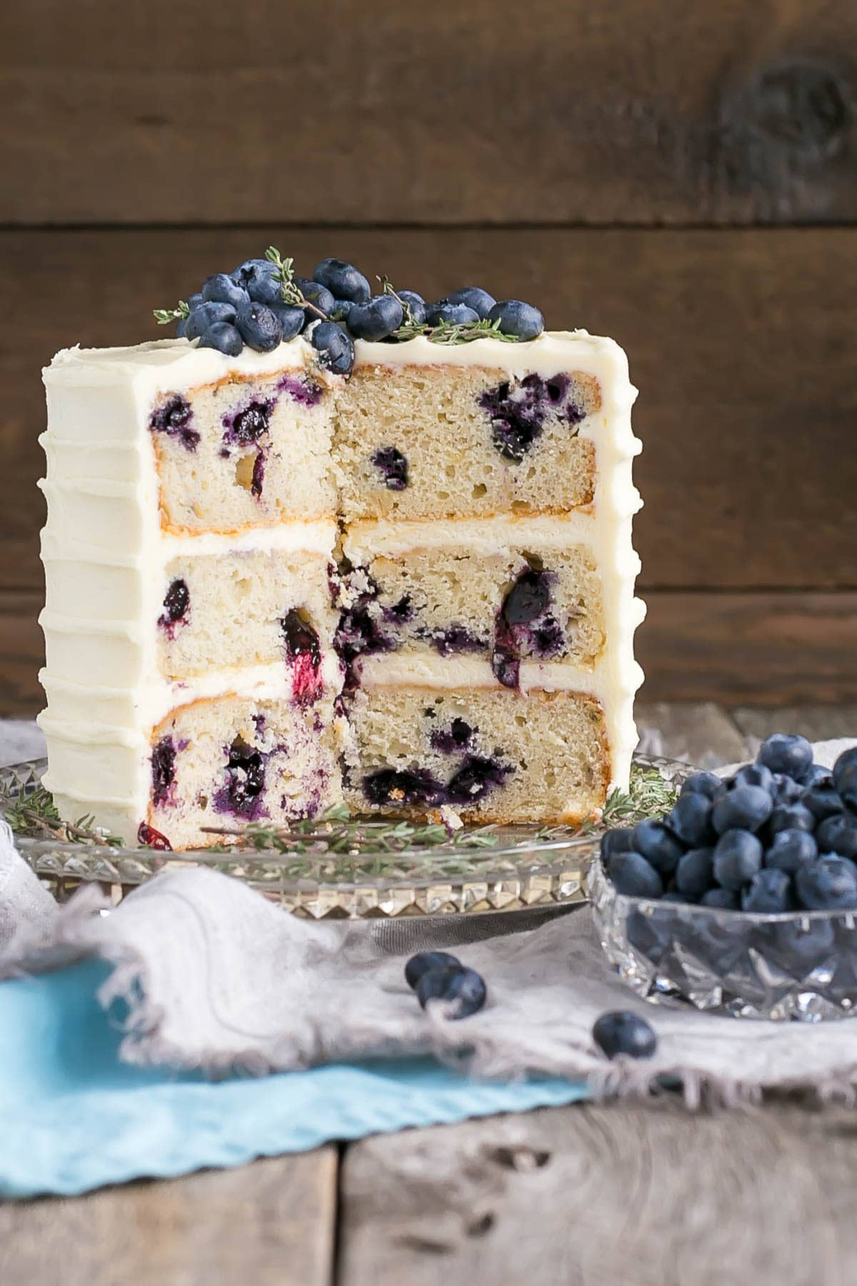 Blueberry Banana Cake with Cream Cheese Frosting with slices cut out.