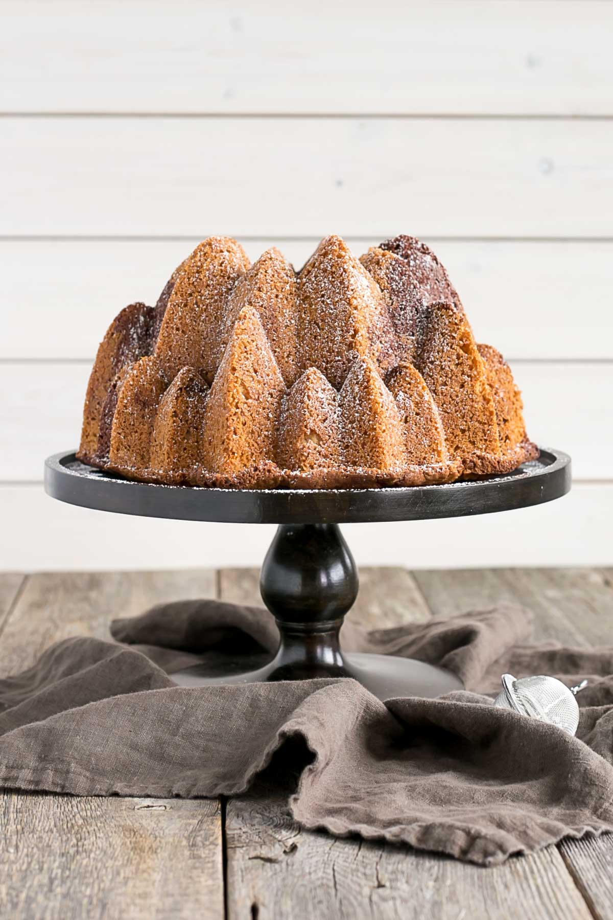 Bundt cake on a wooden cake stand.