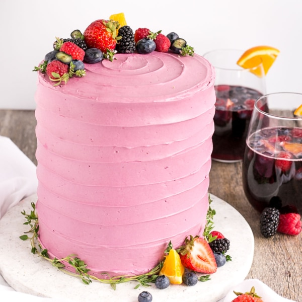 Celebrate summer with this Sangria Cake! Cake layers infused with sangria and orange zest, topped with vanilla buttercream and fresh berries. | livforcake.com