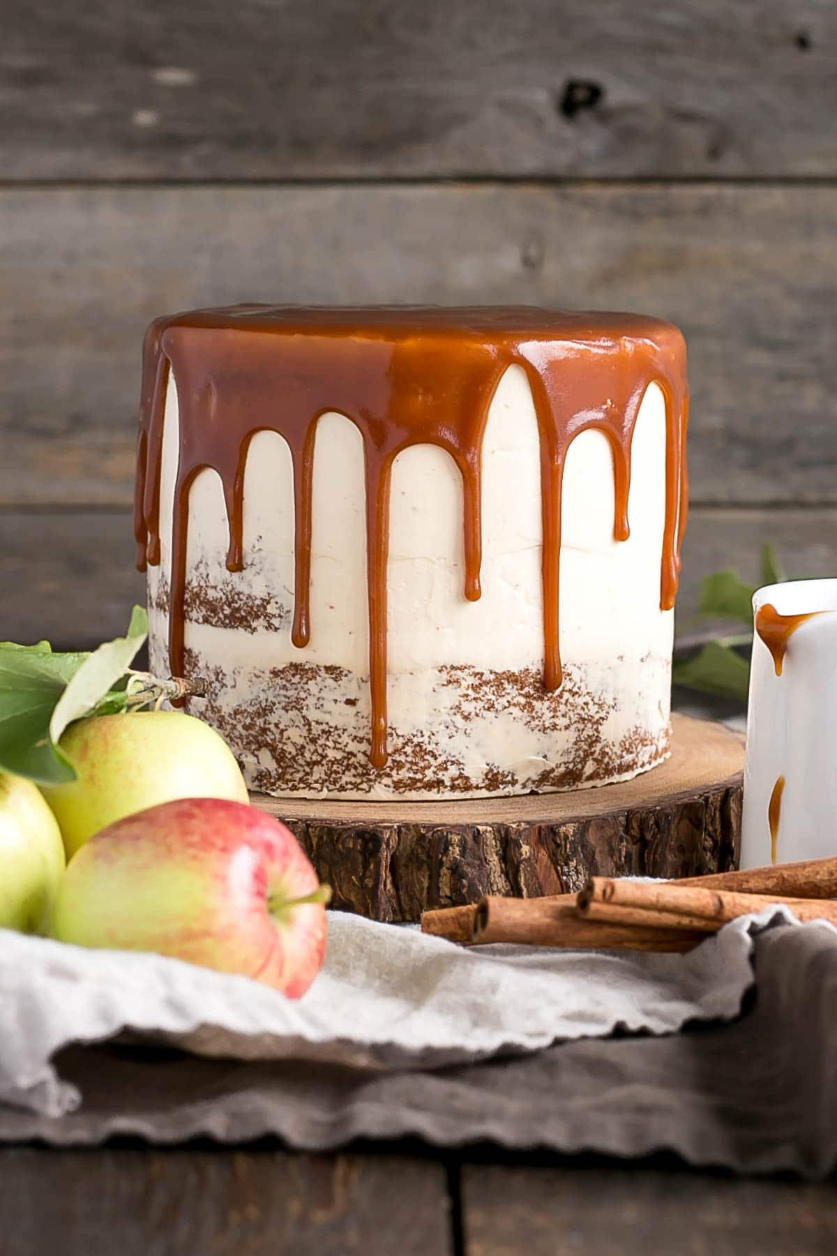 Cake with a caramel drip on a rustic cake stand.