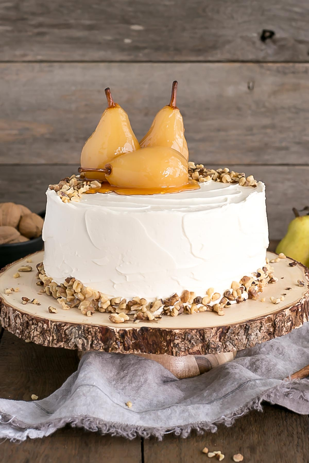 Walnut cake with poached pears on top on a rustic wooden cake stand.