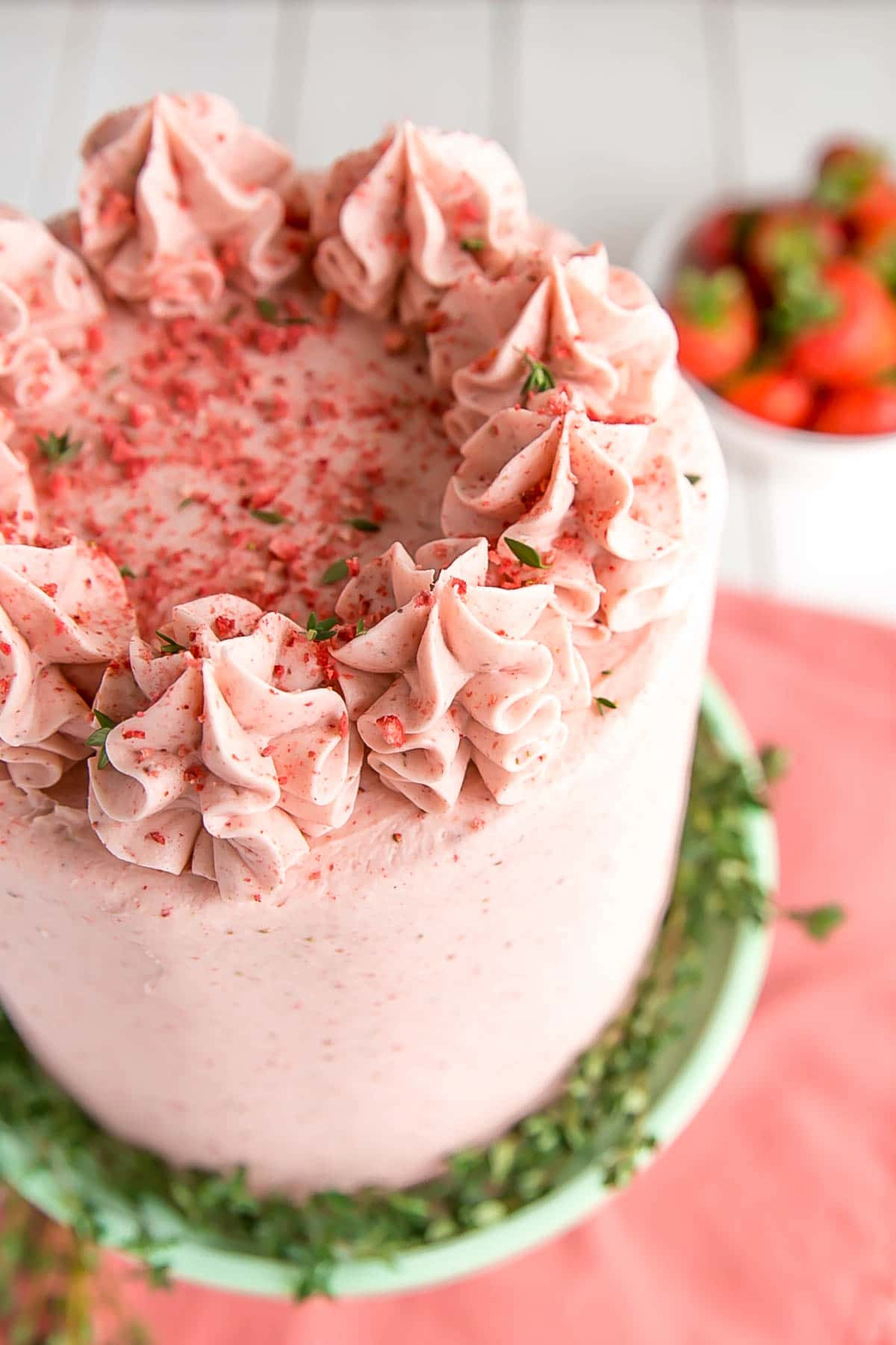 Strawberry cake with ruffle dollops on top.