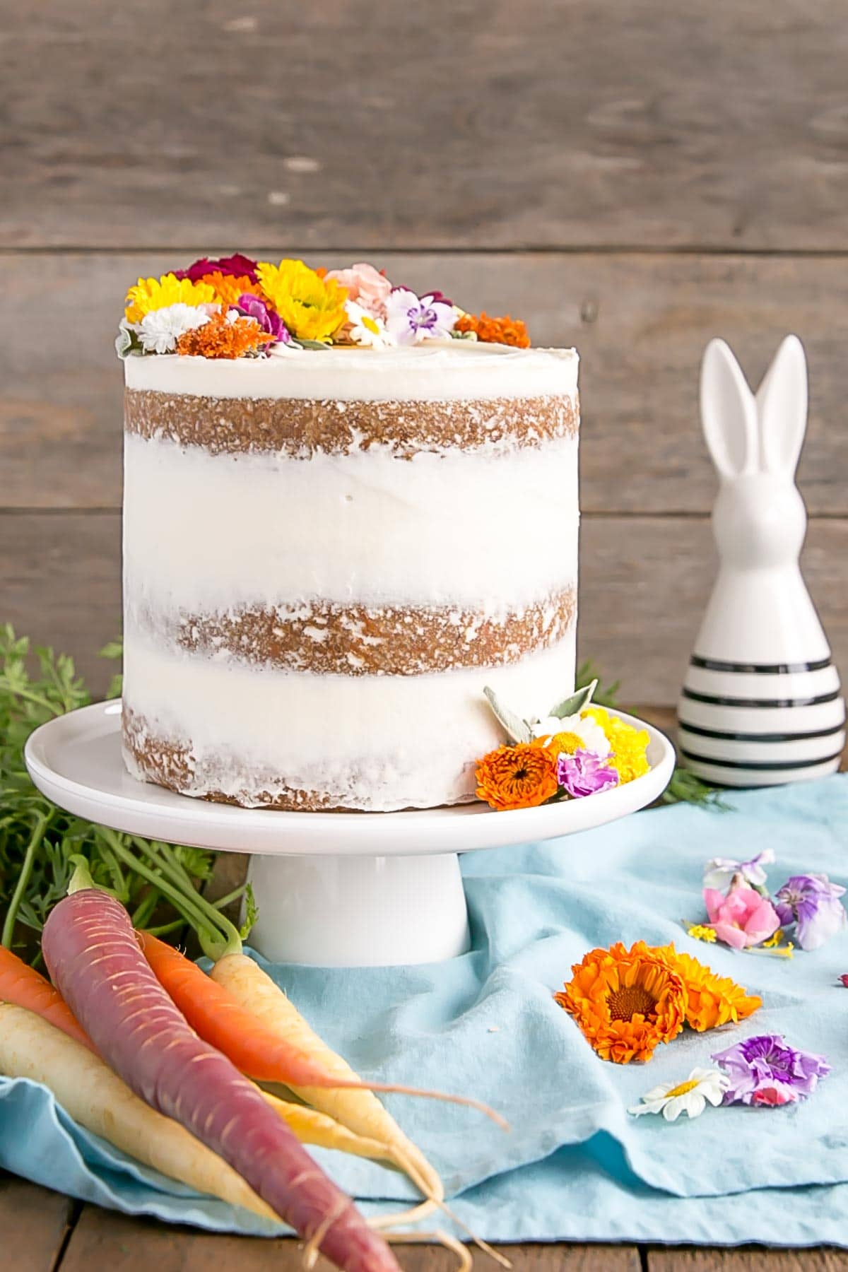 Naked carrot cake front on with ceramic bunny in the background.