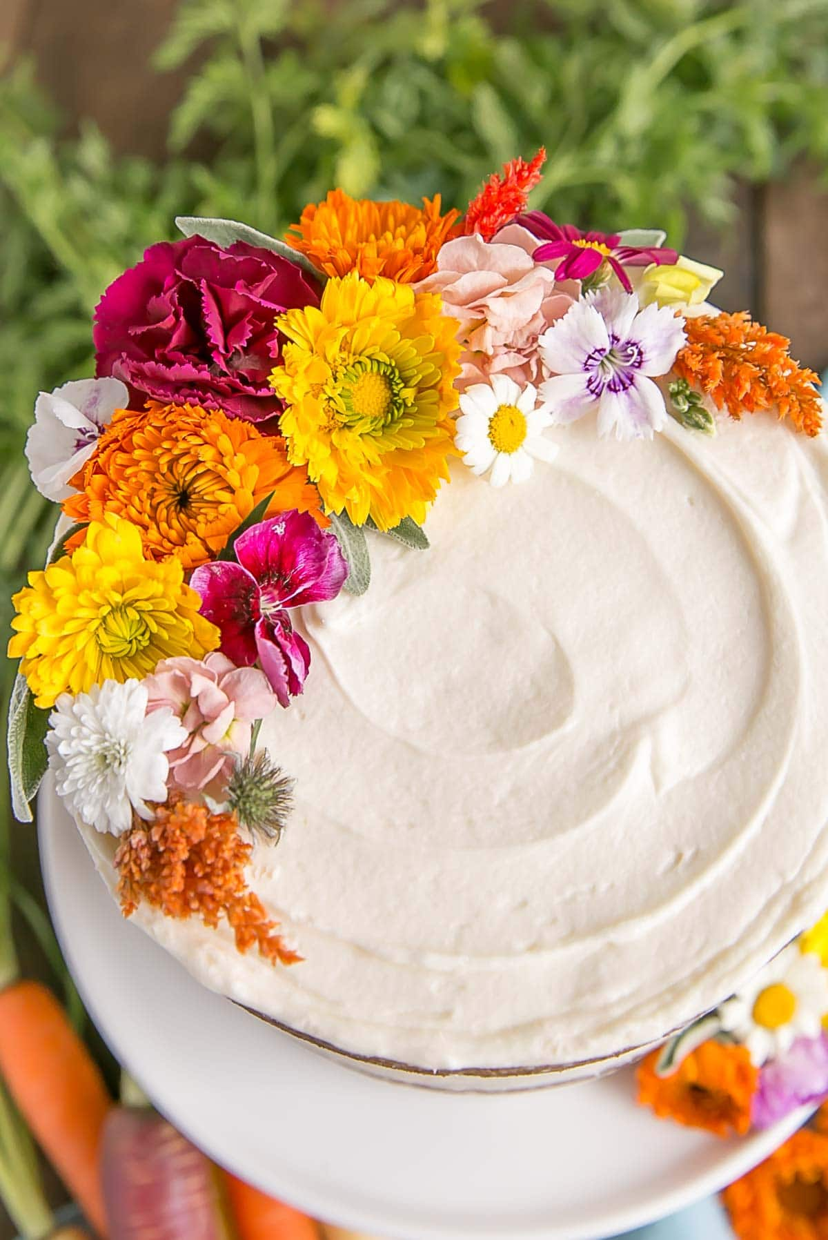 Close up of edible flowers on carrot cake with cream cheese frosting.