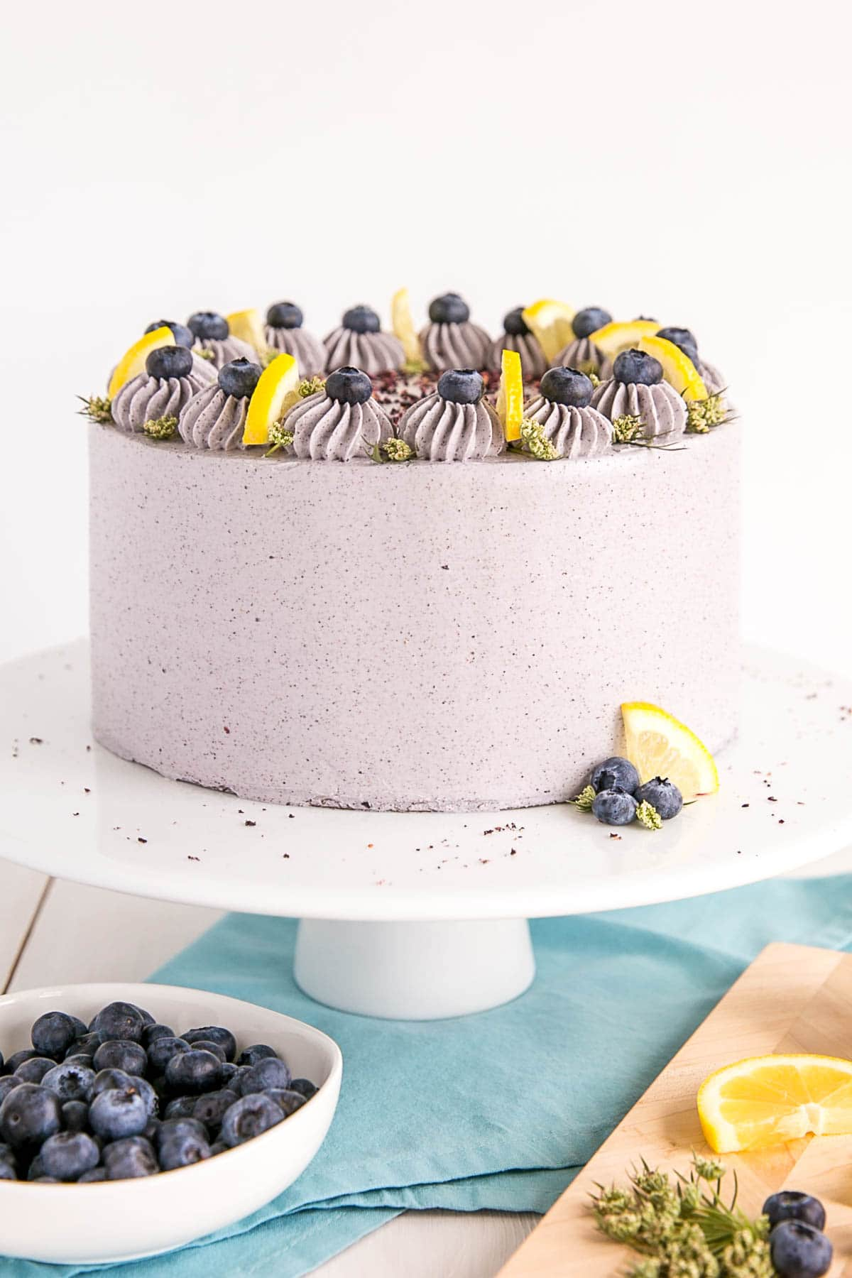 Lemon blueberry cake on a white cake stand decorated with lemon wedges and blueberries.